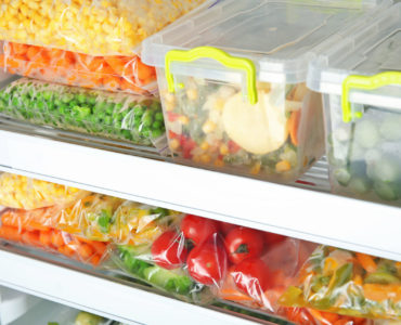 Containers And Plastic Bags With Deep Frozen Vegetables In Refri